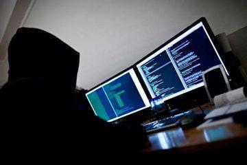 En anonym person sitter framför tre datorskärmar