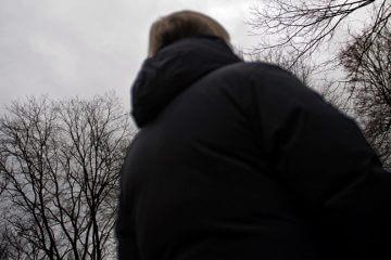 En okänd kvinna tittar upp mot en gråmulen himmel