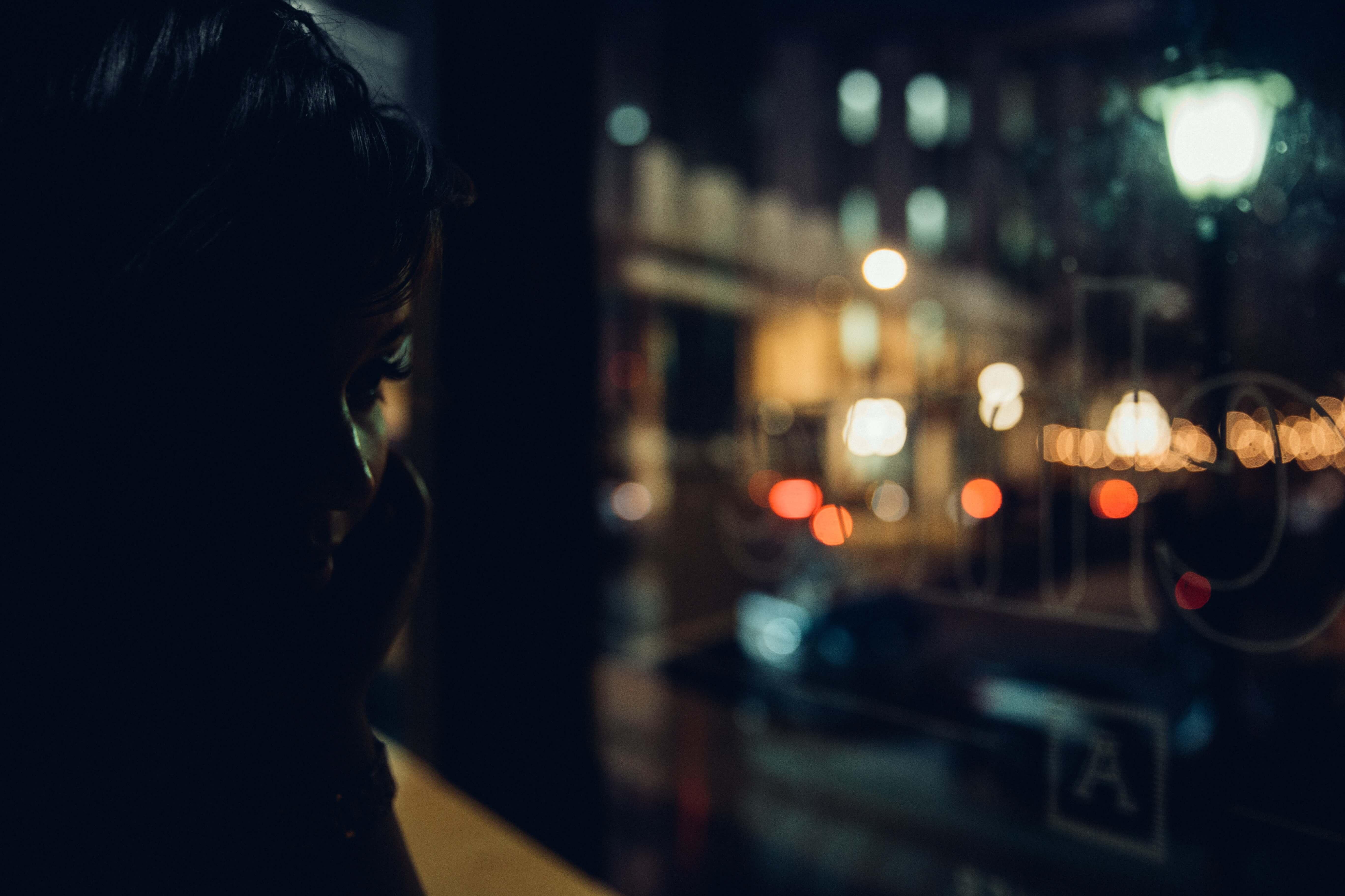 En okänd kvinna står framför ett fönster med ansiktet dolt